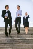 Three happy business people walking together outside. Three business partners standing on stairs and talking Royalty Free Stock Image