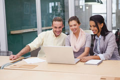 Three happy businessmen working together on a laptop Stock Image