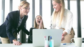 Three happy businesswoman with laptop, high-fiving and cheering