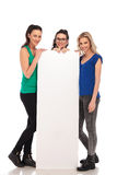 Three happy casual women presenting a big blank board Royalty Free Stock Image