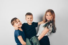 Three happy children against a gray wall. Attractive kids are looking at camera and smiling. Happy amicable family stock image