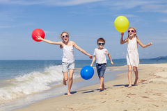 Three happy children with balloons playing on the beach at the d Stock Photography