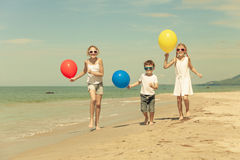 Three happy children with balloons  runing on the beach at the d Royalty Free Stock Photography