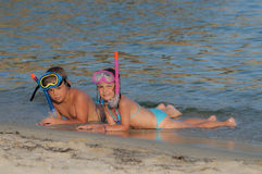 Three happy children on beach with colorful face masks Stock Photography