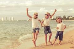 Three happy children dancing on the beach Stock Photo