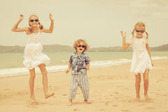 Three happy children dancing on the beach Stock Images