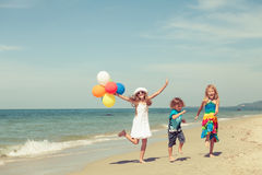 Three happy children dancing on the beach at the day time Stock Images