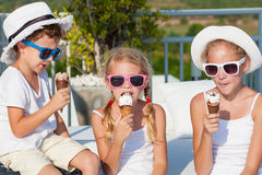 Three happy children eating ice cream near swimming pool at the Stock Photos