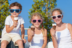 Three happy children eating ice cream near swimming pool at the Royalty Free Stock Image