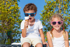 Three happy children eating ice cream near swimming pool at the Royalty Free Stock Photo