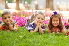 Three happy children lying on the grass Royalty Free Stock Photography