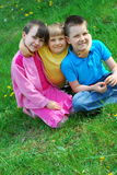 Three happy children in meadow stock image