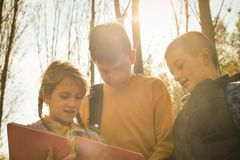 Three happy children in the park. Little girl reading book. royalty free stock photography