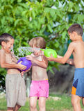 Three happy children play and splashes with water in a park or h Stock Photo