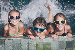 Three happy children  playing on the swimming pool at the day ti Stock Image