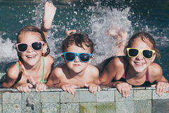 Three happy children  playing on the swimming pool at the day ti Stock Photography