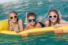 Three happy children playing on the swimming pool at the day tim Stock Photo