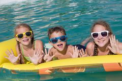 Three happy children playing on the swimming pool at the day tim Stock Photos