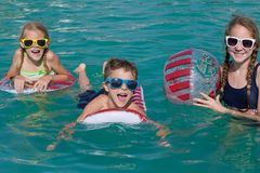 Three happy children playing on the swimming pool at the day tim Royalty Free Stock Image