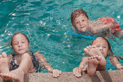 Three happy children playing on the swimming pool at the day tim Royalty Free Stock Photos