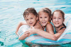 Three happy children playing on the swimming pool at the day tim Royalty Free Stock Images