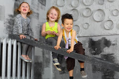 Three happy children sitting on the stairs Stock Photos