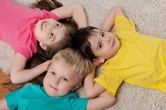 Three happy children on the white carpet Royalty Free Stock Image