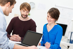 Three happy co-workers in a meeting Royalty Free Stock Photo