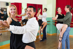 Three happy couples dancing tango. Smiling people dancing tango in the hall. Selective focus royalty free stock photo