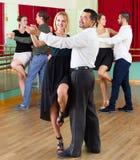 Three happy couples dancing tango Stock Photos