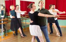 Three happy couples dancing tango Stock Image