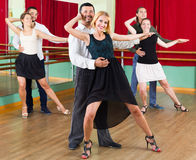 Three happy couples dancing tango Stock Photos