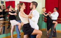 Three happy couples dancing tango stock images