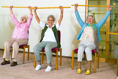 Three happy elderly ladies doing exercises. In a seniors gym sitting in chairs raising wooden poles above their heads while smiling and laughing Royalty Free Stock Image