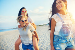 Three happy female friends walking on beach Stock Photography