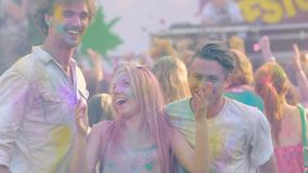 Three happy friends dancing at open air Color festival , enjoying life, slow-mo