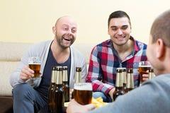 Three happy friends drinking beer. Three happy  positive friends drinking beer and talking at home Royalty Free Stock Photo