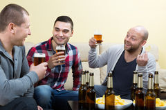 Three happy friends drinking beer. Talking and sitting on couch at home Stock Images