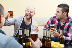 Three happy friends drinking beer. Three happy young guys drinking beer and talking at home Royalty Free Stock Photo