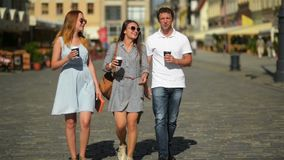 Three happy friends drinking coffee while walking around the city. Full height portrait of two girls and one boy with