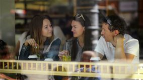 Three Happy Friends Drinking and Having a Good Time at Dinner Table in Cafe with Cocktails. One Man and Two Pretty. Beautiful Women Sitting near Large Window in stock video footage