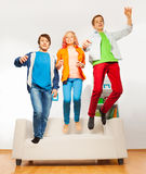 Three happy friends jumping on white sofa Royalty Free Stock Image