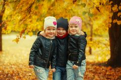 Three Happy Friends Kids Hugging And Laughing In Autumn Park Royalty Free Stock Photos