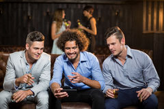 Three happy friends looking at mobile phone while having cigar and whisky stock photography