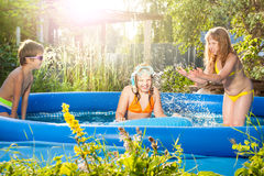 Three happy friends playing in the inflatable pool Royalty Free Stock Photography