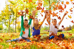 Three happy friends playing with thrown leaves stock photos