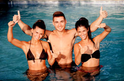 Three happy friends in the pool saying Ok. Three happy friends in the pool with a blue water of background saying Ok stock images