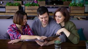 Three happy friends sitting in cafe reading menu and choosing food and beverages. Two women and one man spending lunch. Three happy friends are sitting in cafe stock video footage