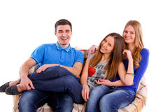 Three happy friends sitting on a couch isolated Stock Photo