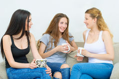 Three happy friends talking and drinking coffee or tea. Three happy friends talking and drinking coffee and tea sitting on a couch at home Royalty Free Stock Images